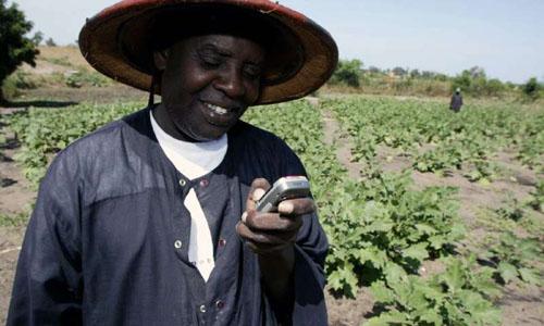 An African farmer using a silver device